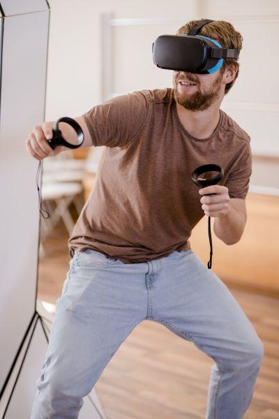 Mann mit Virtual-Reality-Brille und Joysticks in den Händen.