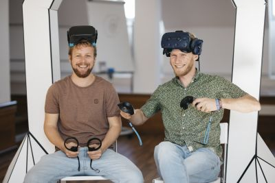 Zwei Männer sitzen auf Stühlen mit Virtal-Reality-Brillen auf der Stirn.