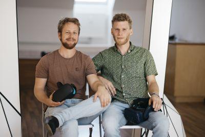 Zwei Männer sitzen auf Stühlen mit Virtal-Reality-Brillen in der Hand.