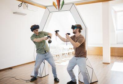 Zwei Männer mit Virtual-Reality-Brillen und Joysticks in der Hand vor weißem Bogen aus Papier.