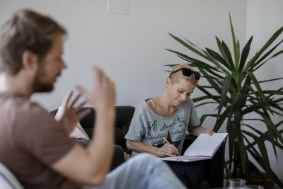 Sigrid Gaisch-Faustmann sitzt in Interviewsituation und schreibt in Block.
