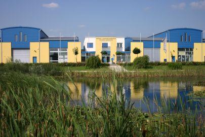 Gebäude in gelb, blau und weiß, davor ein Teich mit Schilf
