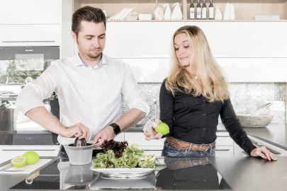 Ein Mann und eine Frau bereiten Salat zu. Der Mann presst eine Limette mit einer herkömmlichen Zitruspresse aus; die Frau hat eine Sprühvorrichtung in eine Limette gesteckt und zeigt dem Mann, wie es auf diese Weise einfacher geht.