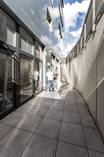 Terrasse von modernem Gebäude, zwei Männer unterhalten sich an Stehtisch