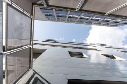 Außenansicht von modernem Gebäude von unten, oben Himmel mit Wolken