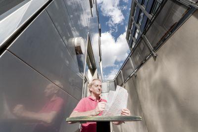 Mann mit Unterlagen hinter Stehtisch zwischen zwei modernen Gebäuden