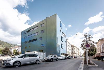 Außenansicht von modernem Gebäude, davor Straße mit parkenden Autos