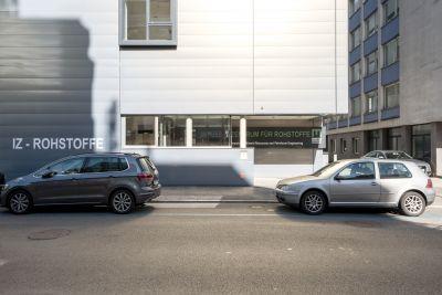 Außenansicht von Gebäude, davor Straße mit parkenden Autos.