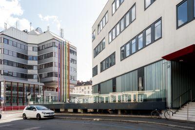 Zwei moderne Gebäude, bunte Stäbe, Schriftzug IZ-WERKSTOFFE