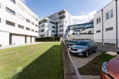 Moderne Gebäude in weiß, mit Glas-Stahl Übergang verbunden, Wiese, Parkplatz