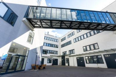 Moderne Gebäude in weiß, mit Glas-Stahl Übergang verbunden, nummerierte Tore