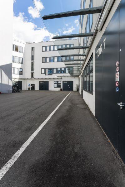 Modernes Gebäude in weiß, nummerierte Tore, Asphalt im Vordergrund