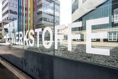 Zwei moderne Gebäude, im Vordergrund groß der Schriftzug WERKSTOFFE