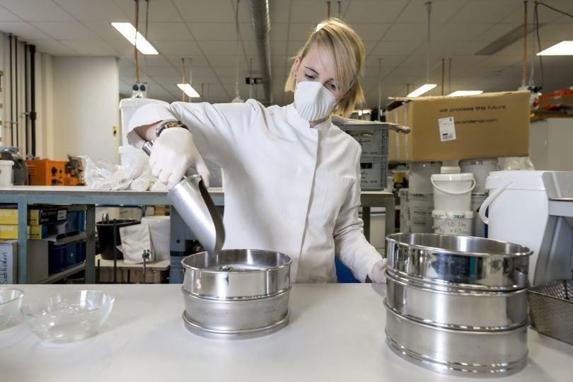 Frau im Labormantel und Mundschutz
