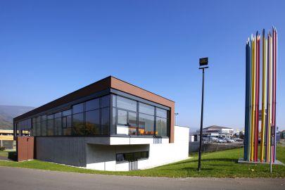 Gebäude in weiß, braun und Glas, gründe Wiese, blauer Himmel, rechts bunte Stäbe