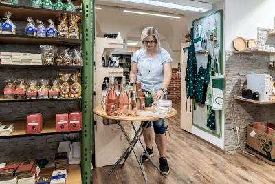 Frau sortiert in Geschäft auf Tisch Lebensmittel in einen Geschenkskorb