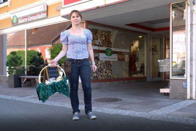Frau steht mit Korb voller Lebensmittel vor Bauern-Genussladen