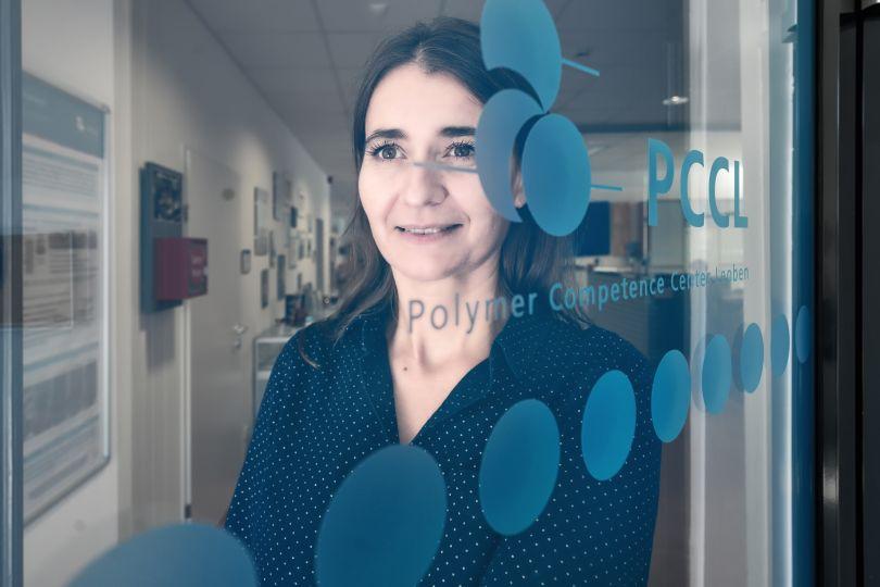 Frau steht hinter Glastür mit der Aufschrift PCCL und runden blauen Kreisen