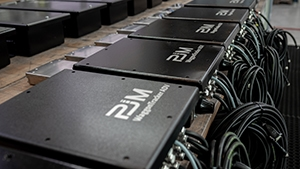 """Fünf gleichartige, schwarze, quaderförmige Geräte, von denen viele Kabeln abzweigen, sind jeweils mit dem Firmenwortlaut """"PJ Monitoring"""" beschriftet."""