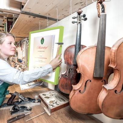 Frau hängt Meisterbrief in Instrumentenbauer-Werkstatt an die Wand