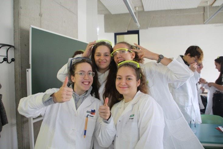 Mädchen in weißen Labormäntel zeigen Daumen hoch
