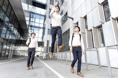Drei Männer gehen, der Mittlere geht in der Luft