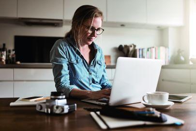 Frau arbeitet in Küche am Laptop