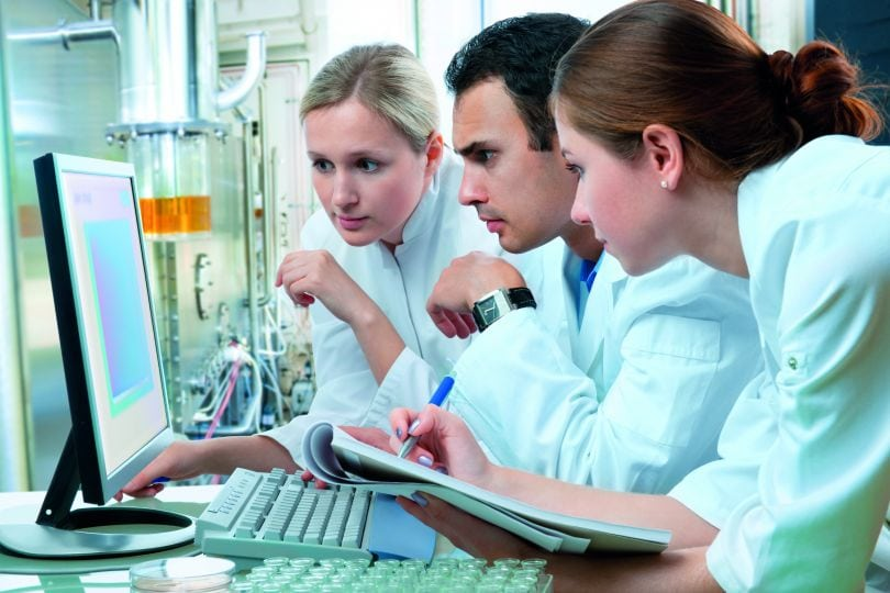 3 Wissenschaftler in Labor vor Computer